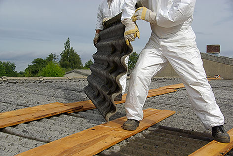 image of asbestos removal specialists removing corrugated roofing made from asbestos containing materials
